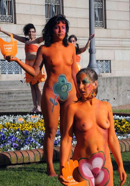 """Women with body paintings and signs reading """"Legal abortion"""", take part in a demo in favour of the legalization of abortion in front of the Congress building in Montevideo on September 25, 2012. The Congress is voting a law project which would decriminilize the interruption of pregnancy under certain conditions, including obliging women to set out before a tribunal the reasons for the abortion.  AFP PHOTO/Miguel ROJO        (Photo credit should read MIGUEL ROJO/AFP/GettyImages)"""