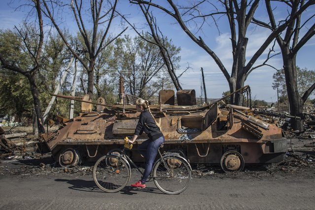 A woman rides a bicycle past the remains of a burnt-out Ukrainian armored personnel carrier (APC) in the village of Lutugine just outside Luhanks, eastern Ukraine, September 14, 2014. (Photo by Marko Djurica/Reuters)