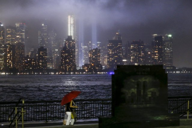 The annual Tribute in Light is tested in New York's Lower Manhattan as a woman walks next to the 9/11 Memorial in Exchange Place, New Jersey, September 10, 2015. (Photo by Eduardo Munoz/Reuters)