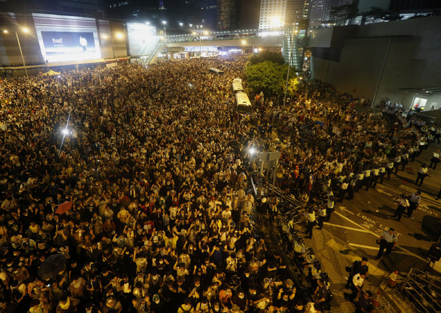 Riot police patrol as tens of thousands of protesters block the main street to the financial Central district (at background) outside the government headquarters in Hong Kong September 28, 2014. (Photo by Bobby Yip/Reuters)