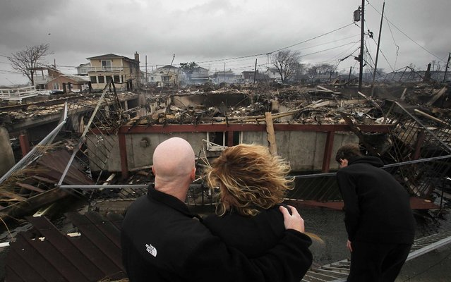 Robert Connolly, left, embraces his wife Laura as they survey the remains of the home owned by her parents  in  Breezy Point. (Photo by Mark Lennihan/Associated Press)