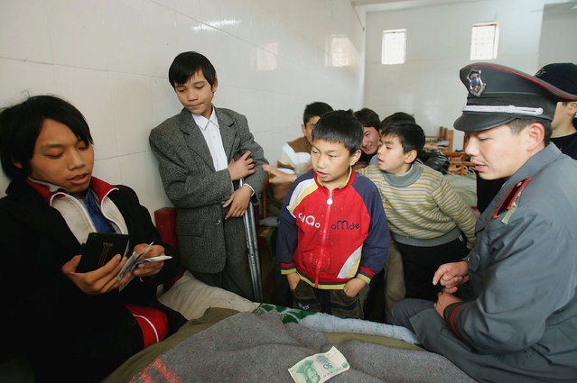 Chinese kids swap money with a beggar (L) under the monitor of a security guard at an assistance center February 23, 2005 in Shenzhen, Guangdong Province, China. (Photo by Cancan Chu/Getty Images)