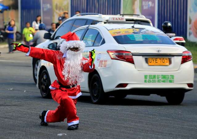 Traffic enforcer Ramiro Hinojas, 51, wears a Santa Claus costume while directing motorists through traffic at an intersection in Pasay City, Metro Manila, Philippines on November 28, 2017. (Photo by Romeo Ranoco/Reuters)
