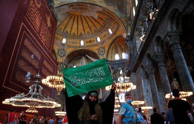 A woman holds a flag as she attends afternoon prayers and visits Hagia Sophia Grand Mosque, for the first time after it was once again declared a mosque after 86 years, in Istanbul, Turkey, July 24, 2020. (Photo by Umit Bektas/Reuters)