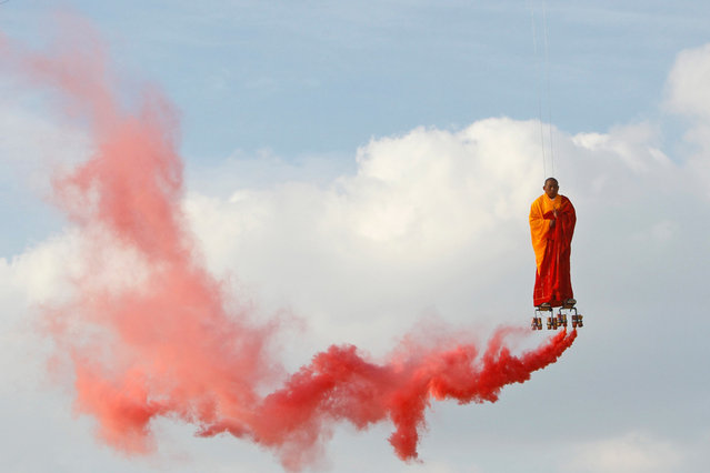 In this March 20, 2012 file photo, suspended by wires, Chinese artist Li Wei performs in the sky at La Villette in Paris. Wei's work often depicts him in apparently gravity-defying situations. (Photo by Francois Mori/AP Photo)