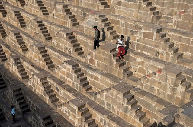 Indian men walk down the steps of the historic Chand Baori stepwell  in Abhaneri village of western Rajasthan state on September 24, 2015. (Photo by Alex Ogle/AFP Photo)