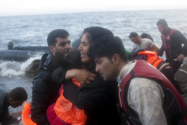 A Syrian refugee family embraces following their arrival on an overcrowded dinghy in rough sea on the Greek island of Lesbos, after crossing a part of the Aegean Sea from the Turkish coast, October 2, 2015. (Photo by Dimitris Michalakis/Reuters)
