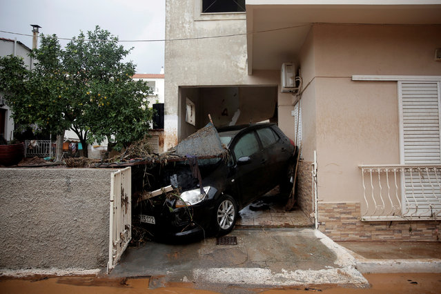 A destroyed car is stuck at the entrance of a house following flash floods which hit areas west of Athens, killing at least 15 people, in Mandra, Greece, November 16, 2017. (Photo by Alkis Konstantinidis/Reuters)