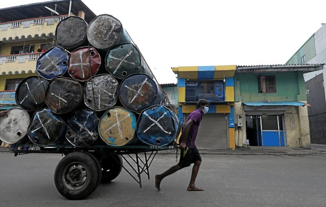 A man wearing a protective mask pulls a cart with metal barrels near a main market, amid concerns about the spread of the coronavirus disease (COVID-19), in Colombo, Sri Lanka, July 30, 2020. (Photo by Dinuka Liyanawatte/Reuters)
