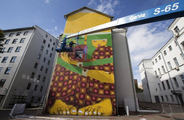 "Gustavo and Otavio Pandolfo, painters representing ""Osgemeos"" (the twins) from Brazil, paint a wall during the street-art festival ""Vulica Brazil"" ahead of celebrations for the Day of Minsk, in Minsk, Belarus, September 7, 2015. (Photo by Vasily Fedosenko/Reuters)"