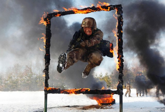 A People's Liberation Army soldier jumps over a burning obstacle during a training session on a snowfield, in Heihe, on November 2, 2014. (Photo by Reuters/Stringer)