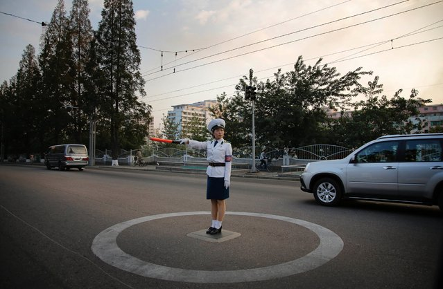 A North Korean traffic police woman directs vehicles at an intersection, Tuesday, September 15, 2015, in Pyongyang, North Korea, as residents commute at the end of the work day. (Photo by Wong Maye-E/AP Photo)