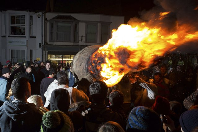 Visitors watch as a burning barrel soaked in tar is carried through the crowds at the annual Ottery St Mary Tar Barrel festival, in Devon, England November 5, 2014. Believed to have its origins in the 1605 Gunpowder Plot, the failed attempt to assassinate King James I of England, the Tar Barrel festival is celebrated yearly in the southwestern English town. (Photo by Daniel Leal-Olivas/Reuters)