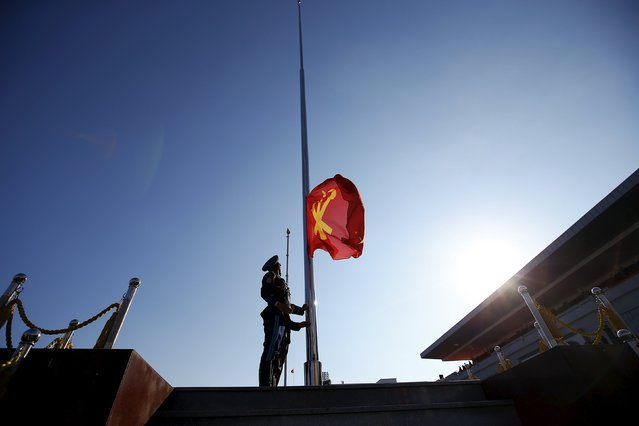 A North Korean soldier lifts a flag of the Workers' Party of Korea at the start of the parade celebrating the 70th anniversary of its founding in Pyongyang October 10, 2015. (Photo by Damir Sagolj/Reuters)