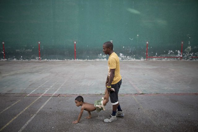 A man helps a child exercise before a wrestling practice session at an old Basque ball gymnasium in downtown Havana, October 20, 2014. (Photo by Alexandre Meneghini/Reuters)