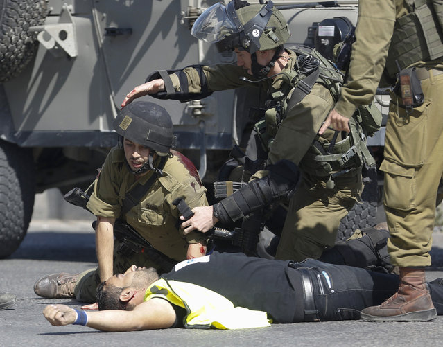 """A wounded Israeli soldier kneels over the body of Palestinian who stabbed him during clashes in Hebron, West Bank Friday, October 16, 2015. The Palestinian man wearing a yellow """"press"""" vest and a T-shirt identifying him as journalist stabbed and wounded an Israeli soldier in the West Bank city of Hebron on Friday before being shot dead by troops, the latest in a monthlong spate of attacks. (Photo by Nasser Shiyoukhi/AP Photo)"""