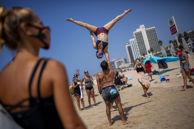 Acrobats perform as they wear face masks during a protest against government's decision to close beaches during the three-week nationwide lockdown due to the coronavirus pandemic, in Tel Aviv, Israel, Saturday, September 19, 2020. Israel went back into a full lockdown on Friday to try to contain a coronavirus outbreak that has steadily worsened for months as its government has been plagued by indecision and infighting. (Photo by Oded Balilty/AP Photo)