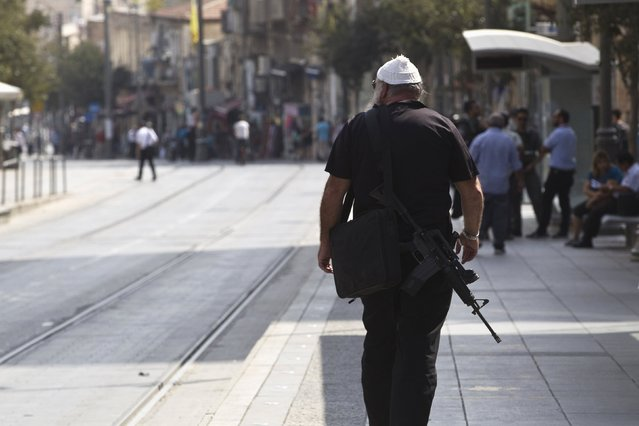 An armed man walks in the centre of Jerusalem October 19, 2015. A surge in Palestinian attacks in Israel is raising concerns that the weakening economy could eventually be pushed into recession. (Photo by Ronen Zvulun/Reuters)