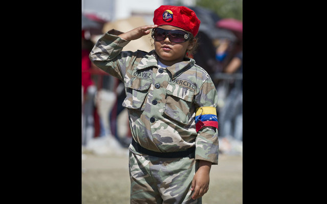 The child dressed as Hugo Chávez, salutes on March 8, 2013. (Photo by Ronaldo Schemidt/AFP Photo)