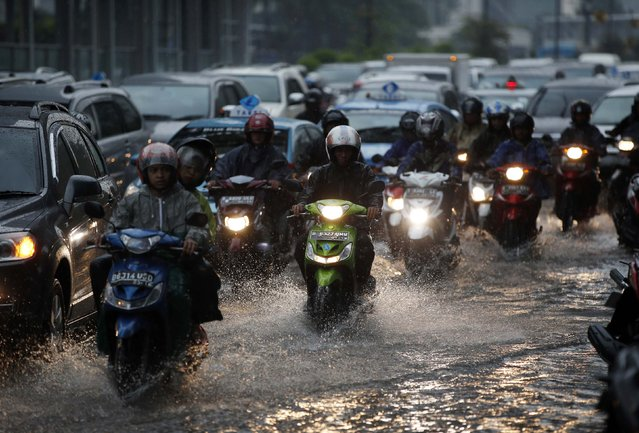 Motorists make their way through a flooded section of a street after a heavy downpour from seasonal rains in central Jakarta November 28, 2014. (Photo by Darren Whiteside/Reuters)