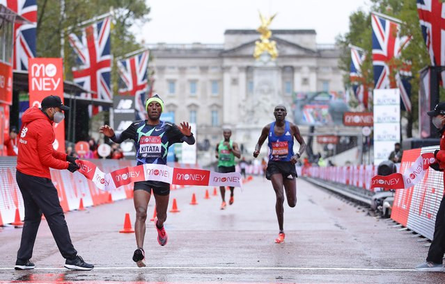 """Ethiopia's Shura Kitata (2nd L) breaks the tape as he wins the elite men's race of the 2020 London Marathon in central London on October 4, 2020. This year's London marathon, an elite-athlete only event, takes place in a """"secure biosphere"""" on a enclosed, looped course, in St James's Park, due to coronavirus restrictions. (Photo by Richard Heathcote/Pool via AFP Photo)"""