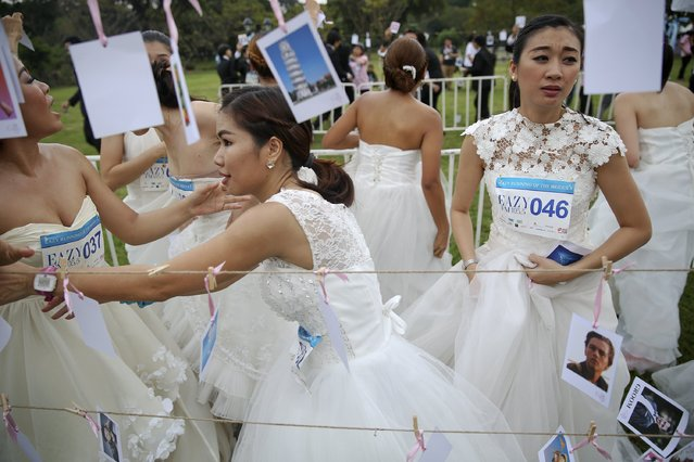 """Brides-to-be participate in a stage of the """"Running of the Brides"""" race in a park in Bangkok November 29, 2014. (Photo by Damir Sagolj/Reuters)"""