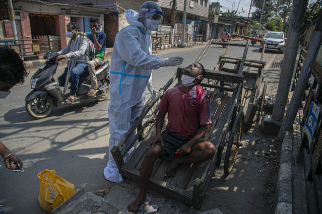 A health worker takes a nasal swab sample of a cartpuller during random testing for COVID-19 in a market in Gauhati, India, Friday, October 16, 2020. India's coronavirus fatalities jumped by 895 in the past 24 hours, a day after recording the lowest daily deaths of 680 in nearly three months. The Health Ministry on Friday also reported 63,371 new cases in the past 24 hours, raising India's total to more than 7.3 million, second in the world behind the U.S. (Photo by Anupam Nath/AP Photo)