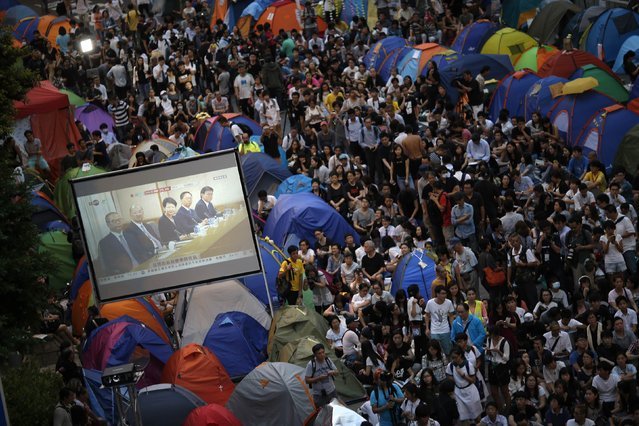 Pro-democracy protesters watch formal talks between student protest leaders and government officials on a video screen near the government headquarters in Hong Kong, in this October 21, 2014 file photo. (Photo by Carlos Barria/Reuters)