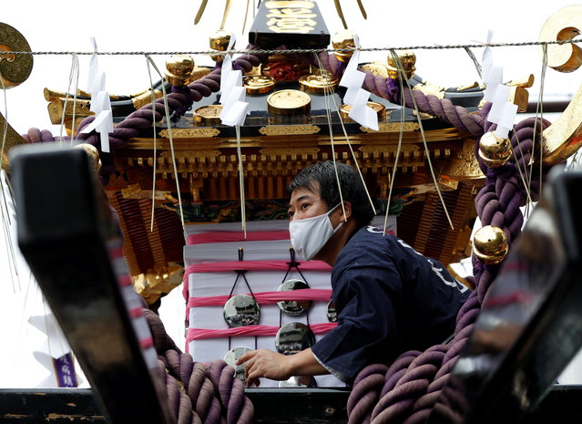 A reveller wearing a protective mask tries to load a Mikoshi or portable shrine onto a truck, while it's usually carried by the hands of revellers, under the infection control measures during Sanja Matsuri, one of the Tokyo's biggest traditional festivals, taking place after months of delay caused by the coronavirus disease (COVID-19) outbreak, at Asakusa district in Tokyo, Japan on October 18, 2020. (Photo by Issei Kato/Reuters)