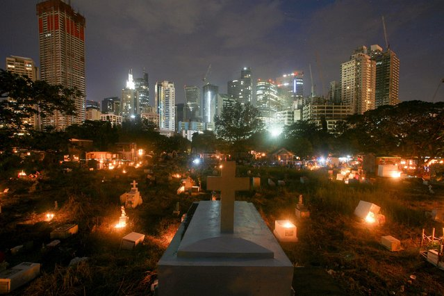 Candles illuminate graves inside a public cemetery in Makati's financial district of Manila November 1, 2015. (Photo by Janis Alano/Reuters)