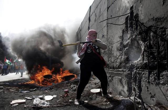 A female Palestinian demonstrater uses an axe to try and destroy a part of the Israeli controvertial separation wall separating the West Bank city of Abu Dis from east Jerusalem, during clashes with Israeli security forces, on November 2, 2015. (Photo by Ahmad Gharabli/AFP Photo)
