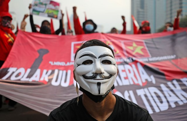A masked protester pauses during a protest against the new Job Creation Law in Jakarta, Indonesia, Friday, October 16, 2020. Dozens of activists staged the protest demanding that the government revoke the law they say will cripple labor rights. (Photo by Dita Alangkara/AP Photo)