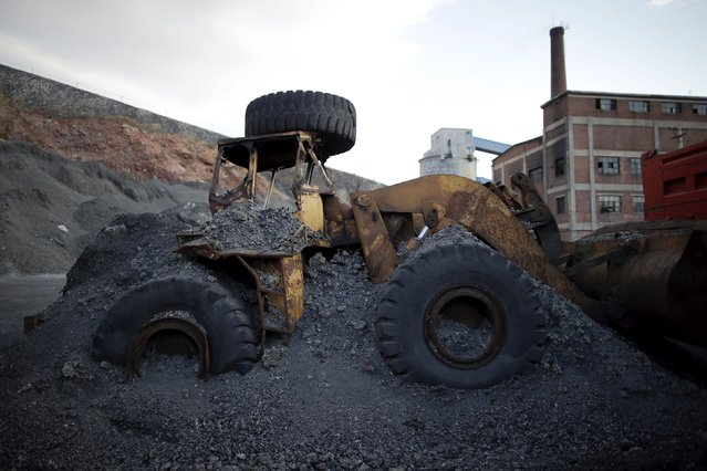 An abandoned excavator is partially covered by coal waste at a coal mine of the state-owned Longmay Group on the outskirts of Jixi, in Heilongjiang province, China, October 24, 2015. (Photo by Jason Lee/Reuters)
