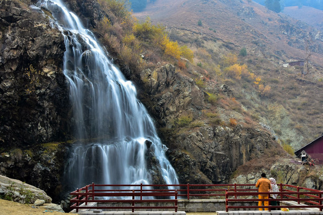 Visitors explore the waterfalls on an autumn day in Drang about 40kms from Srinagar, the summer capital of Jammu and Kashmir on November 12, 2020. (Photo by Saqib Majeed/SOPA Images/Rex Features/Shutterstock)