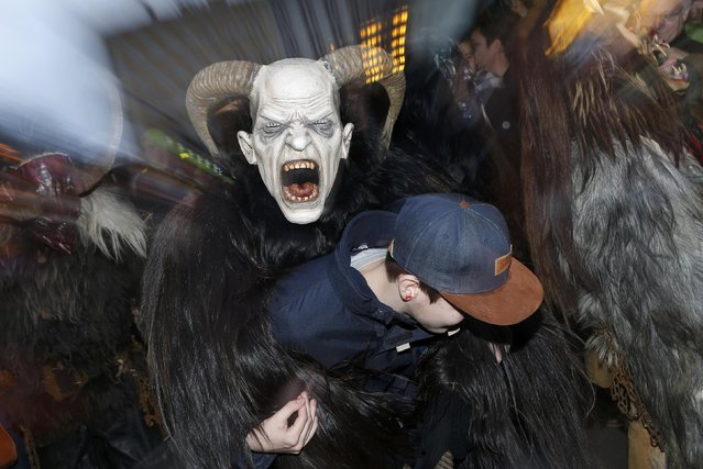 """A man dressed as """"Krampus"""" creature takes part in a parade at Munich's Christmas market, December 14, 2014. Young single men will wear the traditional attires known as """"Krampus"""", consisting of animal skins and masks, with large cow-bells to make loud and frightening noises and parade through the city. They follow 'Saint Nicholas' from house to house in December each year to bring luck to the good and punish the idle. (Photo by Michaela Rehle/Reuters)"""