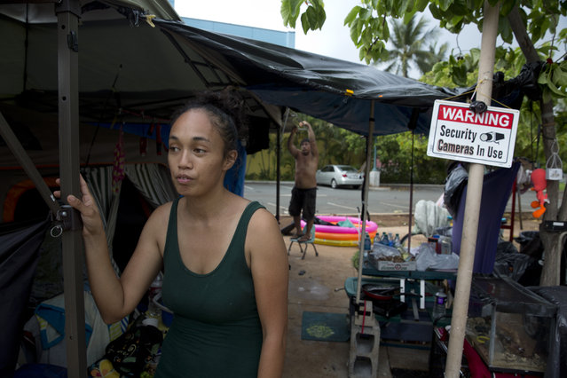 In this Wednesday, August 26, 2015 photo, Tabatha Martin, 27, stands in front of her makeshift tent while her husband, Tracy, background, prepares their shelter for an approaching storm at a homeless encampment in the Kakaako district of Honolulu. The Martins said they became homeless when Tracy had a heart attack after working long hours as a kitchen manager. After exhausting their savings, they couldn't afford rent for their Pearl City apartment and wound up on the street. (Photo by Jae C. Hong/AP Photo)