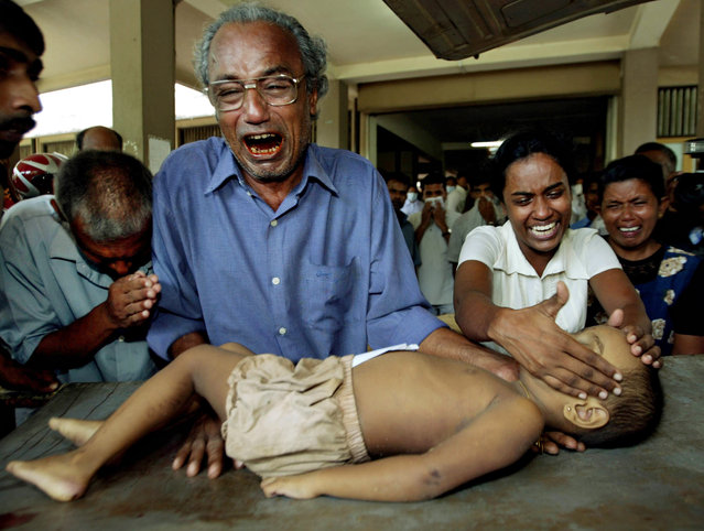 In this December 27, 2004 file photo, a young tsunami victim's father cries as he holds the body of his son along with other family members at the Galle Hospital in Galle, Sri Lanka. (Photo by Vincent Thian/AP Photo)
