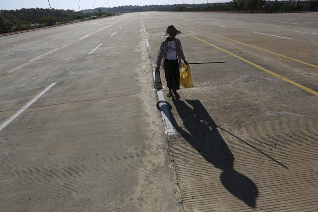 A worker walks along the almost emptied twenty-lane road in front of parliament in Naypyitaw November 14, 2015. (Photo by Soe Zeya Tun/Reuters)