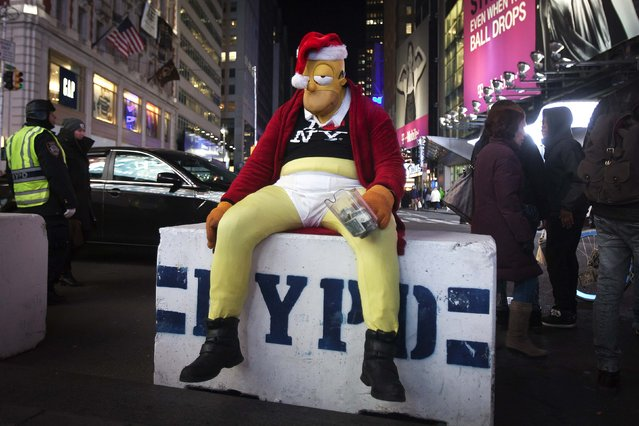 A person dressed as cartoon character Homer Simpson sits on an NYPD security barricade in Times Square as preparations are made for New Years Eve in New York December 29, 2014. (Photo by Carlo Allegri/Reuters)