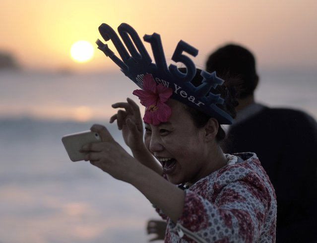 A tourist reacts after taking a picture of the sun as New Year's revellers welcome the first sunrise of 2015 on Sydney's Bondi beach, January 1, 2015. (Photo by Jason Reed/Reuters)