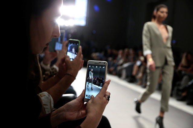Audience take photos of a model presenting a creation by Greek designer Dimitrios Ordoulidis during the 10th Athens Exclusive Fashion Week in Athens, Greece, October 22, 2016. (Photo by Alkis Konstantinidis/Reuters)
