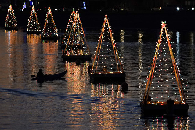 A kayaker paddles among holiday lights, Wednesday, December 16, 2020, in Long Beach, Calif. (Photo by Ashley Landis/AP Photo)