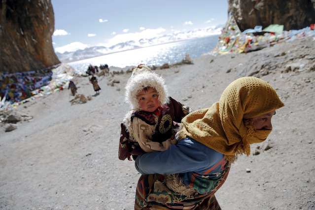 A Tibetan woman carries a child as they visit Namtso lake in the Tibet Autonomous Region, China November 18, 2015. (Photo by Damir Sagolj/Reuters)