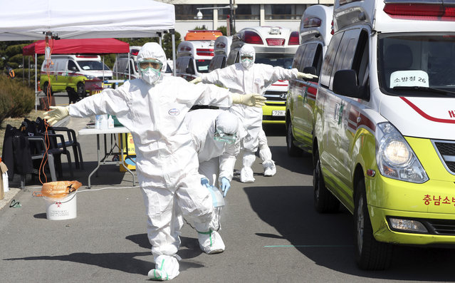 """Members of paramedics wearing protective gears are disinfected near their ambulances in Daegu, South Korea, Friday, March 6, 2020. Seoul expressed """"extreme regret"""" Friday over Japan's ordering 14-day quarantines on all visitors from South Korea due to a surge in viral infections and warned of retaliation if Tokyo doesn't withdraw the restrictions. (Photo by Kim Hyun-tai/Yonhap via AP Photo)"""