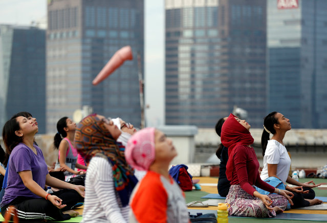 People take part in a sunrise yoga class on the helicopter landing pad on the roof of the Grand Sahid Jaya hotel in Jakarta, Indonesia September 25, 2016. (Photo by Darren Whiteside/Reuters)