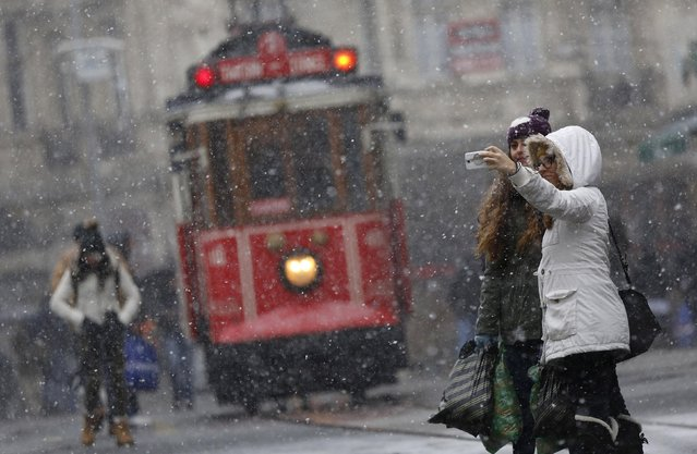 """Pedestrians, with a vintage tram in the background, take a """"selfie"""" as snow falls at the main shopping street of Istiklal in central Istanbul January 6, 2015. (Photo by Murad Sezer/Reuters)"""