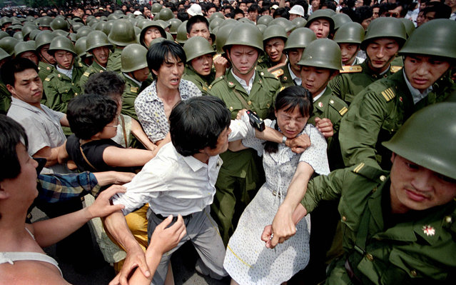 Student protestors, including one girl with a camera, struggle with soldiers from the Chinese Army, the PLA. Tiananmen Square, 1989. (Photo by Jeff Widener/Associated Press)