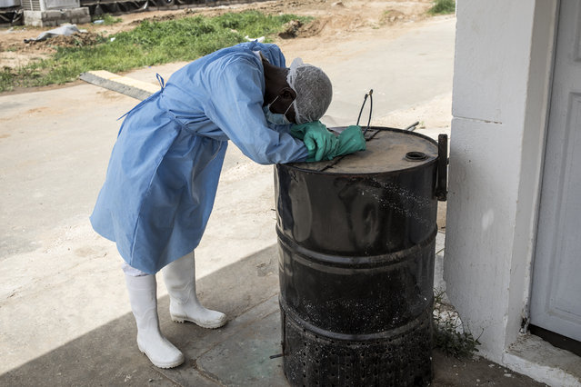 A hygienist rests as he waits outside a decontamination area in a COVID-19 coronavirus treatment centre that cares for positive patients that show little or no symptoms in Dakar on June 26, 2020. (Photo by John Wessels/AFP Photo)