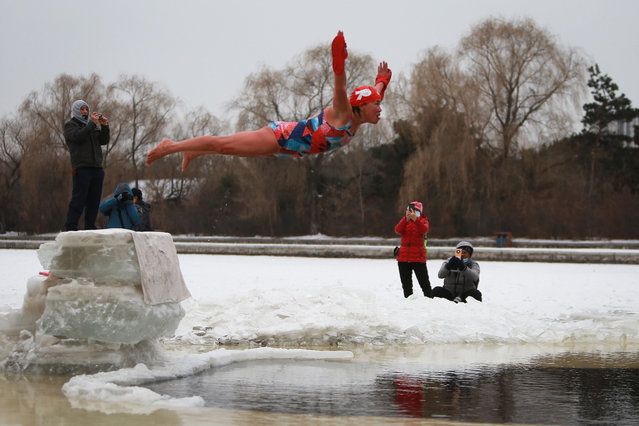 A winter swimming enthusiast jumps into a partly frozen lake in Shenyang, in northeastern China's Liaoning province on January 20, 2021. (Photo by AFP Photo/China Stringer Network)