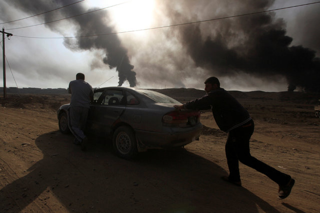 Displaced people push their car as smoke rises from oil wells, set ablaze by Islamic State militants before fleeing the oil-producing region of Qayyara, Iraq, November 4, 2016. (Photo by Alaa Al-Marjani/Reuters)